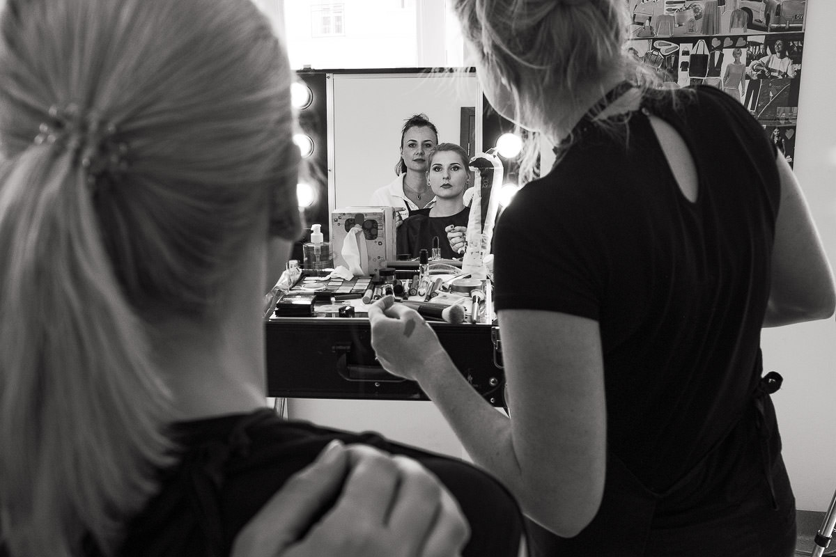 girl sitting in front of the makeup mirror