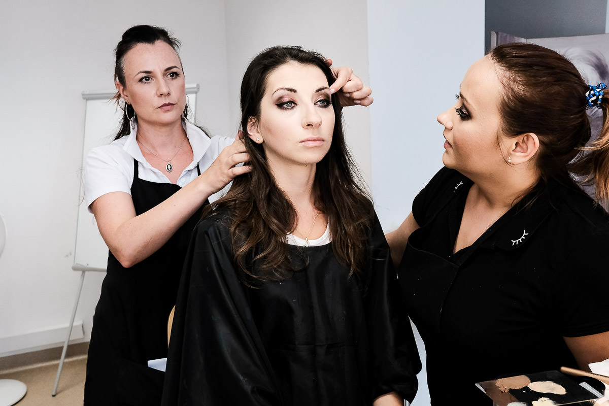 make up artist showing how to apply eye lashes