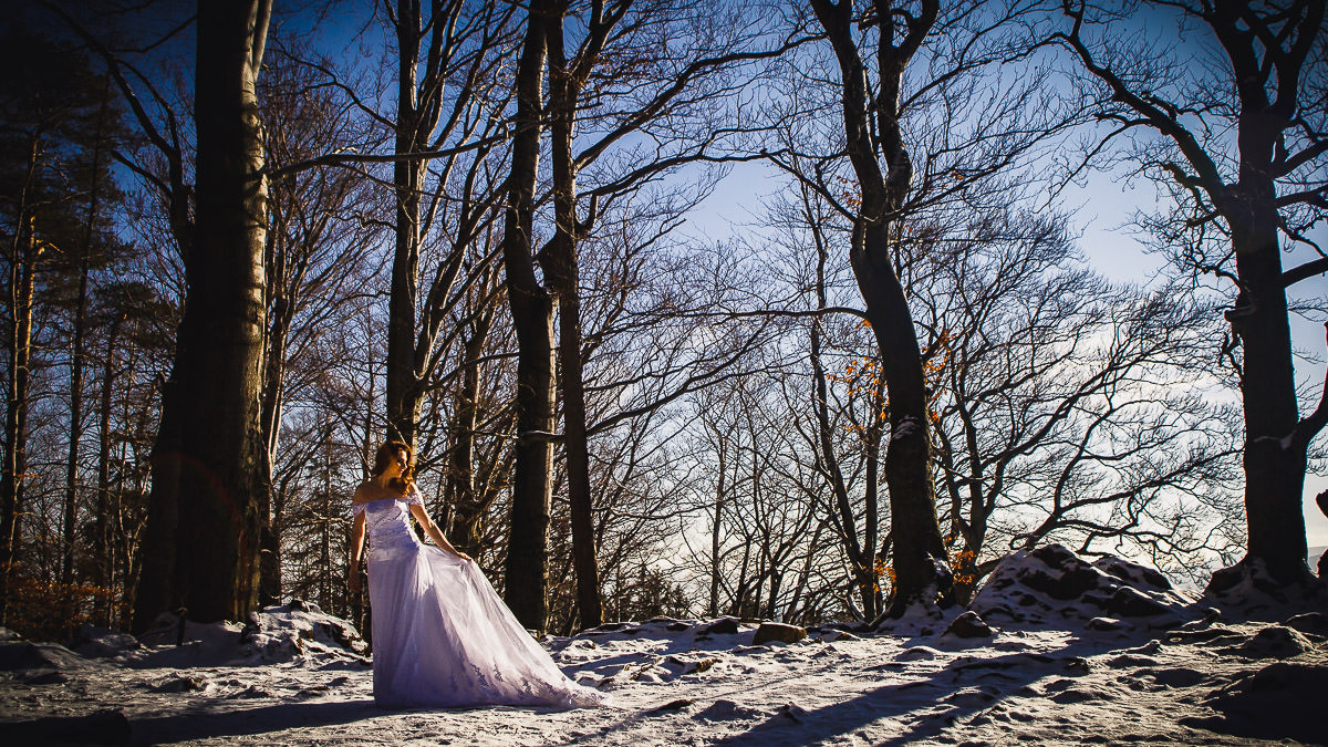 bride in her dress surrounded by snow